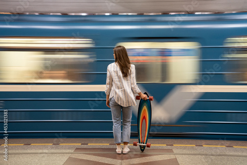 Obraz na plátně Woman wait for metro car at subway station with train passing by on background