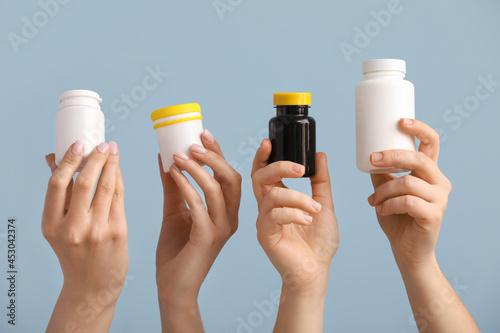 Fotografering Women with medical bottles on color background
