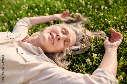 Fotografia Woman with drooping eyelids lying on grass