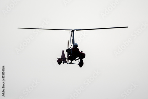 Tela Flying autogyro silhouette on white background.