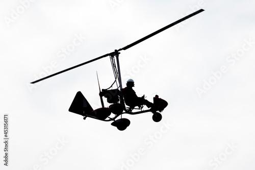 Murais de parede Flying autogyro silhouette on white background.
