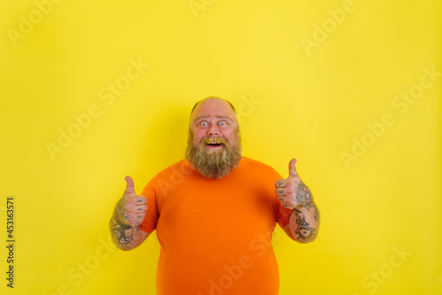 Fotografia Happy man with beard and tattoos does a positive gesture with hands