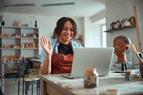 Fototapeta Cheerful female potter using laptop in pottery workshop