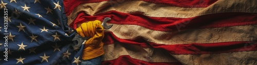 Fototapeta Worn work glove holding wrench tool and gripping old worn US American flag