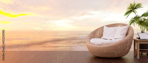 Photo Wicker round chair, portable tablet on table, sunset over sea in background
