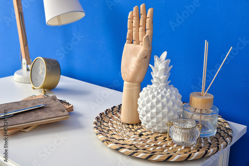 Stylish decor and reed diffuser on table near color wall Fototapeta
