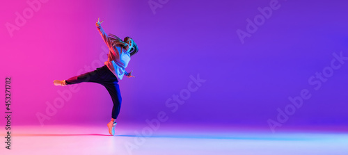Foto Attractive young girl dancing hip-hop isolated on gradient pink purple neon stud