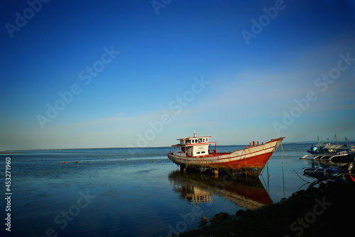 Fotografiet Scenic view of a traditional fishing boat on a shallow coast under a clear sky
