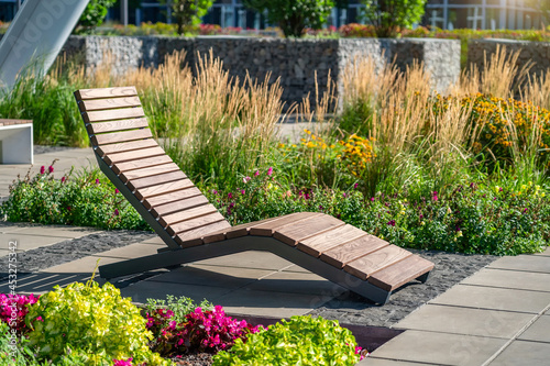 Empty brown wooden deck chair or chaise longue on tile among decorative grass and flowers in recreation area Fototapet