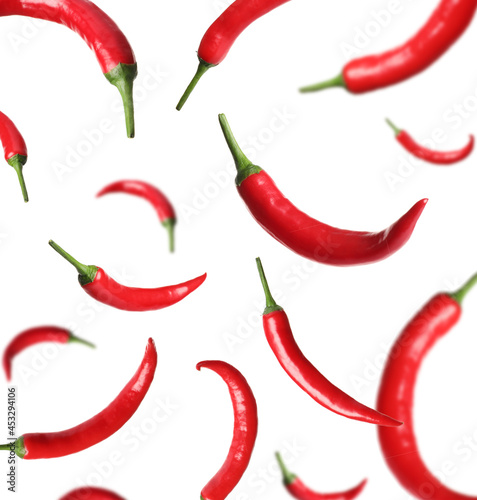 Ripe red chili peppers falling on white background Fotobehang