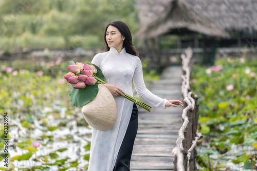 Portrait of beautiful vietnamese woman with traditional vietnam hat holding the Fototapeta
