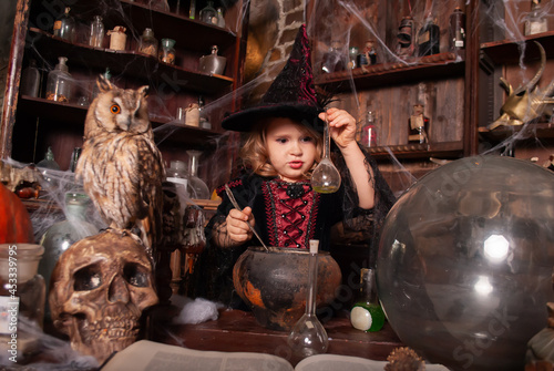 Canvas Print girl charming little witch conjuring potions for Halloween with an assistant oy