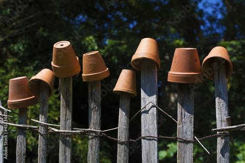 Canvas Print Vieille clôture dans un jardin protégée par des pots en terre cuite