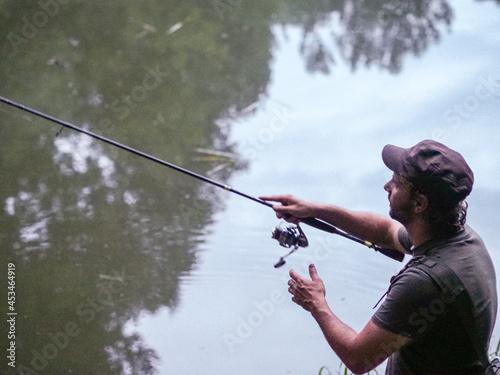 Shallow focus of an Italian man casting a fishing rod on a calm lake Fototapet