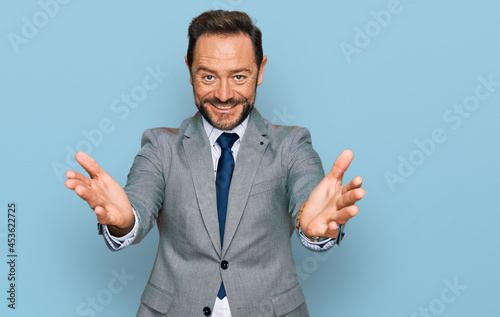 Fotografiet Middle age man wearing business clothes looking at the camera smiling with open arms for hug