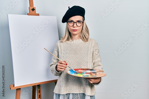 Fototapeta Beautiful caucasian woman drawing with palette on easel stand skeptic and nervous, frowning upset because of problem