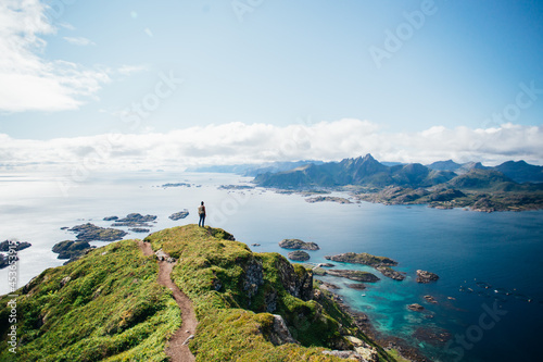 Fototapeta Amazing epic shot of young man hiker stand on top of mountain after long difficult hike in Lofoten Islands in Norway