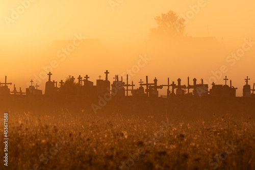 Fototapeta Silhouettes of the crosses of the Catholic cemetery in the early morning at sunrise