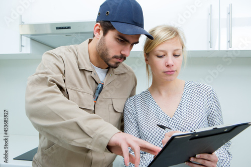 Valokuva tradesman showing customer where to sign her name