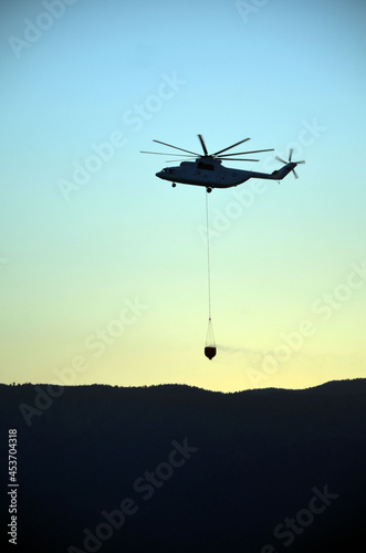 Fotografia Russian  helicopter draws water from the sea to extinguish a forest fire