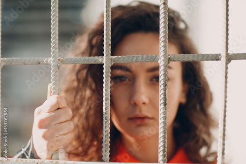 Wallpaper Mural Young brunette curly woman in orange suit behind jail bars