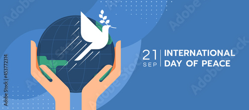Fotografering International day of peace - hands hold circle earth and the dove of peace to fl