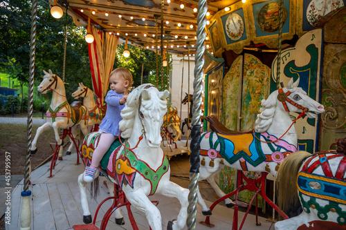 Fotografie, Obraz Cute baby girl on the horse of old retro carousel, Prague, Czech republic