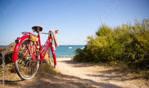 Foto Vieux vélo rouge au bord de la plage et de la mer bleu.
