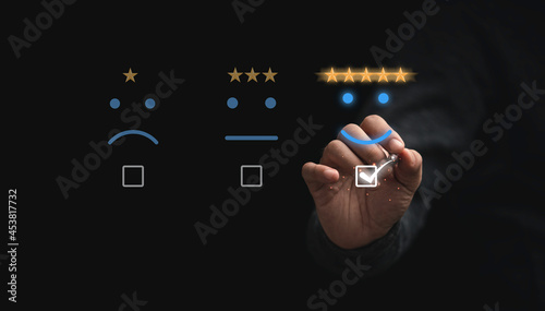 Obraz na plátně Businessman touching button to select five stars with smiley face for the best excellent evaluation of customer satisfaction of product and service concept