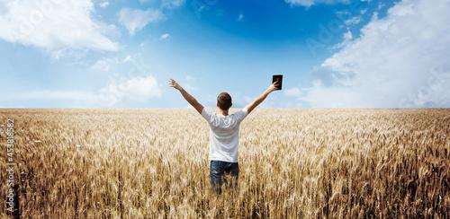 man holding up Bible in a wheat field Fototapet