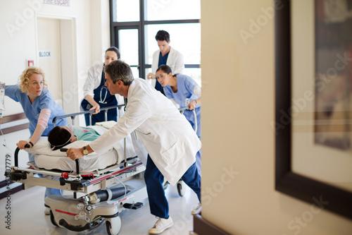 Doctors rushing patient on gurney in hospital corridor