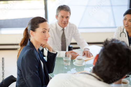 Doctors and businesswoman talking in meeting