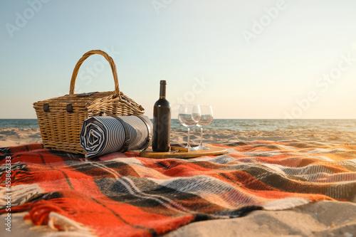 Fotografie, Obraz Blanket with picnic basket, bottle of wine and glasses on sandy beach near sea,