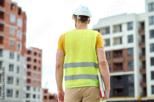 Fotografija Worker in a reflective waistcoat standing on the building site