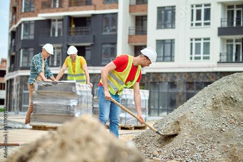 Caucasian male builder in a reflective waistcoat scooping the soil Fototapeta