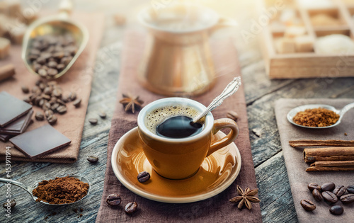 Fotografering A cup of aromatic black coffee, a coffee maker, coffee beans of different varieties on the table