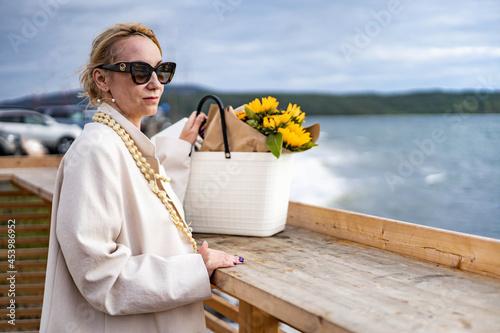 Fashionable relaxed woman contemplating wavy sea from embankment enjoying freedo Fototapete
