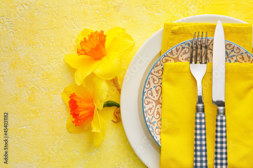 Fotografie, Obraz Beautiful table setting with narcissus flowers on color background