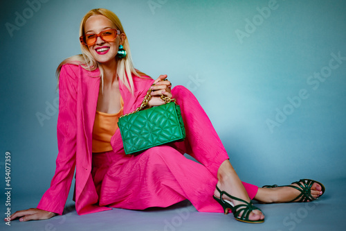 Fotografie, Obraz Happy smiling fashionable woman wearing trendy pink fuchsia color suit, orange sunglasses, strappy sandals, with green quilted casette leather bag