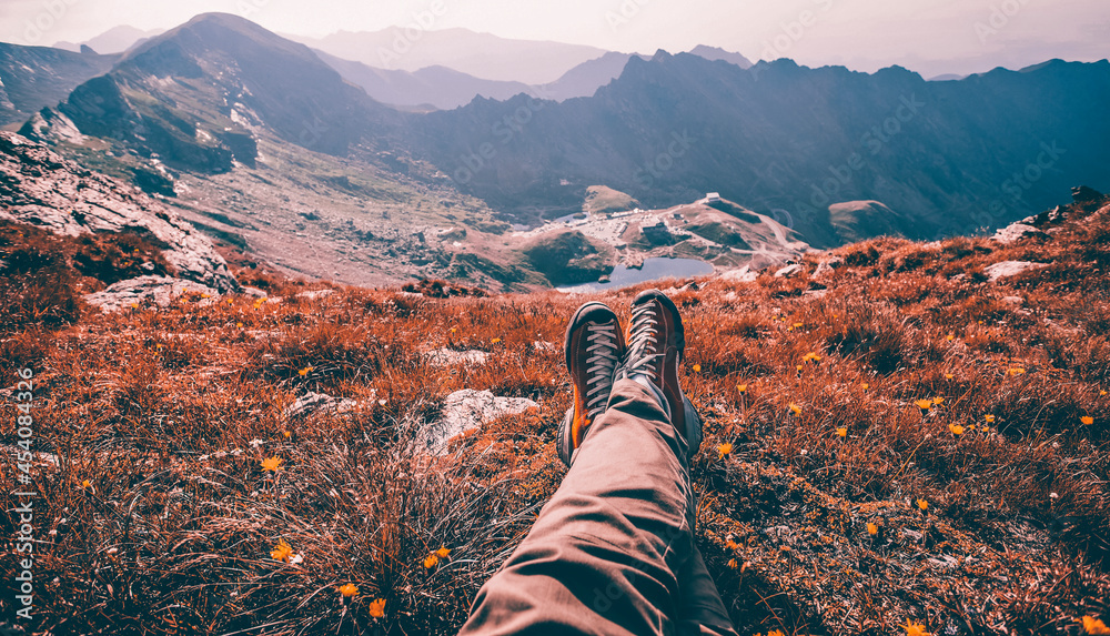 Legs of traveler sitting on a high mountain top in travel