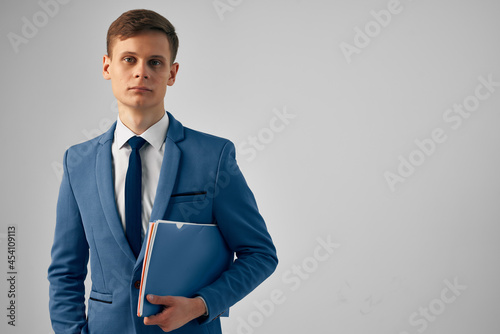 Fotografia, Obraz man in a suit with a blue folder in his hands work office official