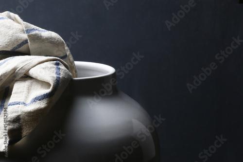 Un vaso in ceramica bianca e uno strofinaccio da cucina; composizione su fondo s Fotobehang
