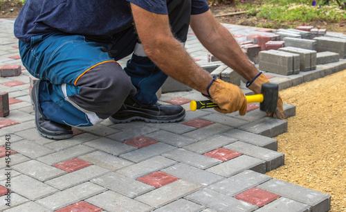 Obraz na plátně A gloved craftsman lays paving stones in layers