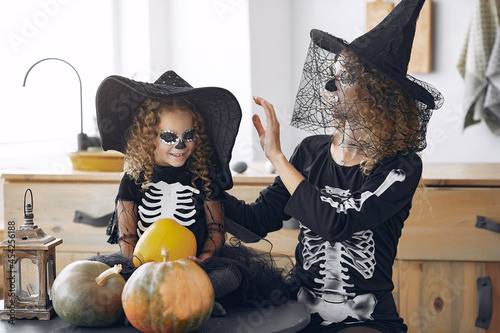 Fototapeta Mother with daughter in a halloween costume and makeup