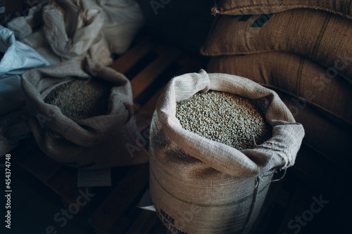 Fotografia Green coffee beans in burlap sack at roaster company.