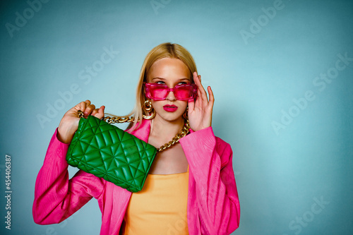 Fototapeta Fashion portrait of confident woman posing with trendy green leather quilted bag, wearing trendy pink fuchsia color rectangle sunglasses