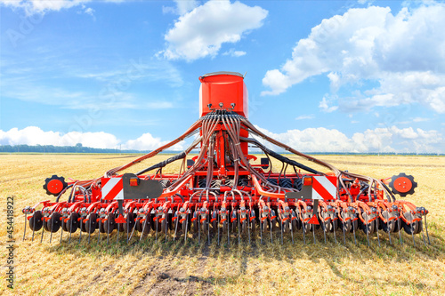 Fotografie, Obraz A multifunctional agricultural harrow stands in a harvested wheat field against a blue cloudy sky on a summer day