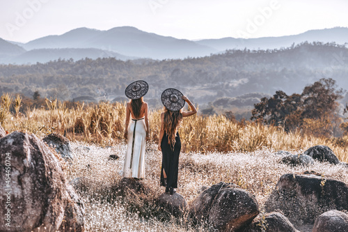 Fototapeta premium two beautiful young woman in elegant dresses on the field at sunset