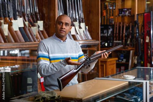 Fototapeta Portrait of hispanic salesman showing collectible old rifled musket on backgroun
