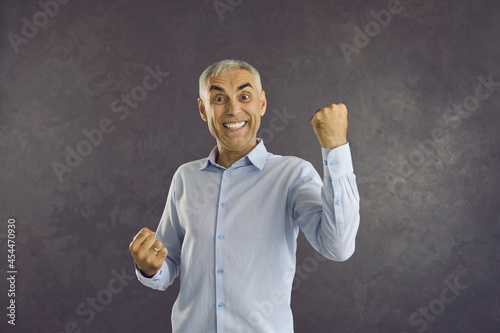 Valokuvatapetti Portrait of overjoyed middle-aged man isolated on black studio background feel euphoric celebrate success win victory